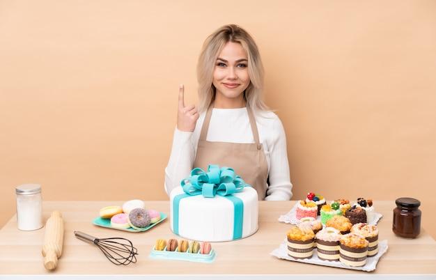 Nastolatek cukiernik z dużym ciastem w stole wskazującym palcem wskazującym to świetny pomysł