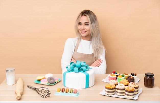 Nastolatek cukiernik z dużym tortem w stole, patrząc z boku