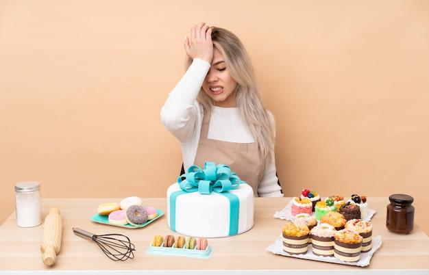 Nastolatek cukiernik z wielkim ciastem w stole, mając wątpliwości z mylącym wyrazem twarzy