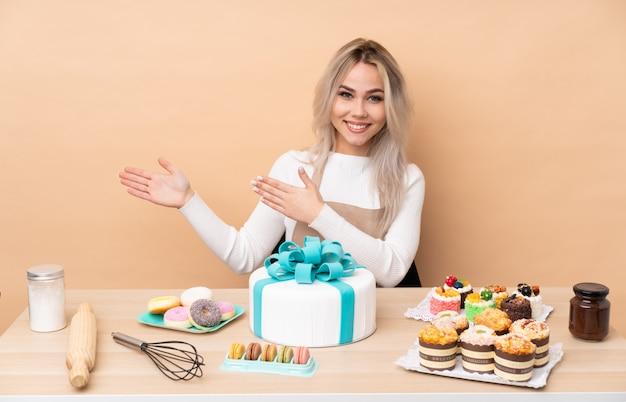 Nastolatek cukiernik z wielkim ciastem w stole rozkładającym ręce na bok za zaproszenie