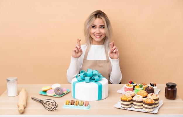 Nastolatek cukiernik z wielkim ciastem w stole z palcami przekraczania