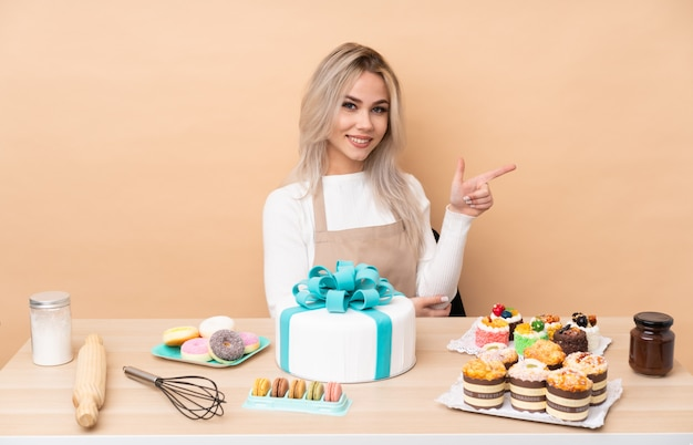 Nastolatek cukiernik z wielkim ciastem w tabeli palcem wskazującym na bok