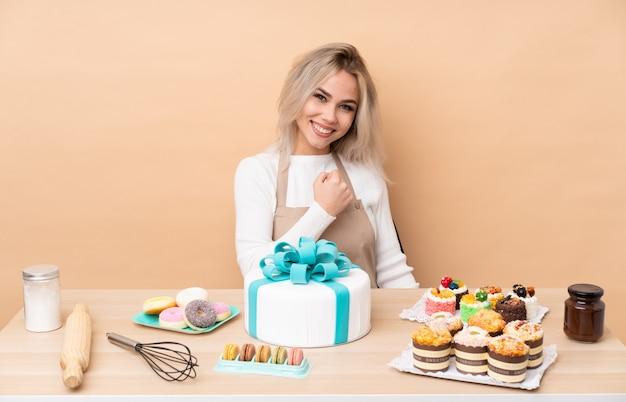 Nastolatek cukiernik z wielkim tortem w stole świętuje zwycięstwo