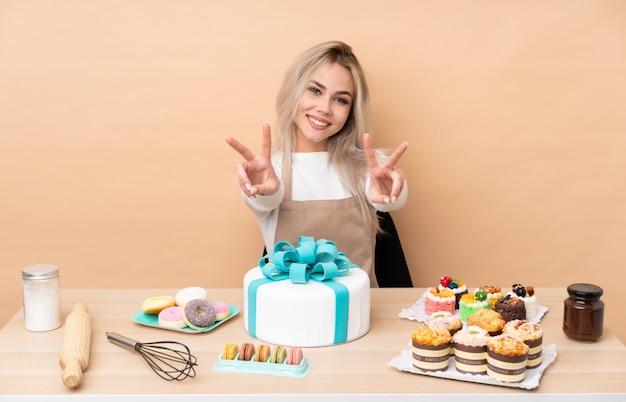 Nastolatek cukiernik z wielkim tortem w stole uśmiecha się znak zwycięstwa i pokazuje