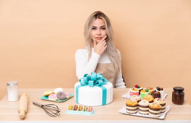 Nastolatek cukiernik z wielkim tortem w stole z pomysłem