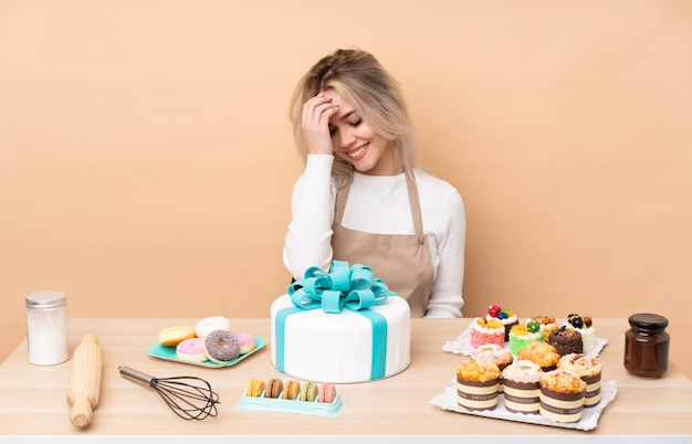 Nastolatek cukiernik z wielkim tortem w tabeli śmiejąc się