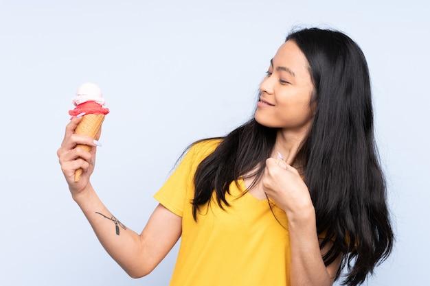 Nastolatek dziewczyna azjatyckich z lodami cornet wyizolowanych na niebiesko świętuje zwycięstwo