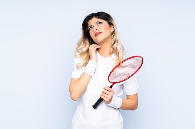 Nastolatek dziewczyna bawić się badminton na błękit ścianie myśleć pomysł