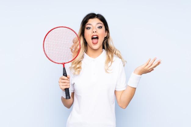 Nastolatek dziewczyna bawić się badminton na błękit ścianie z zdziwionym wyrazem twarzy