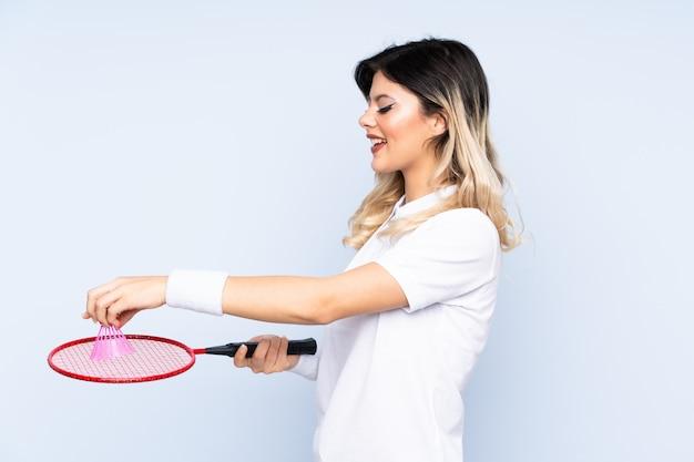 Nastolatek dziewczyna bawić się badminton na błękit ścianie