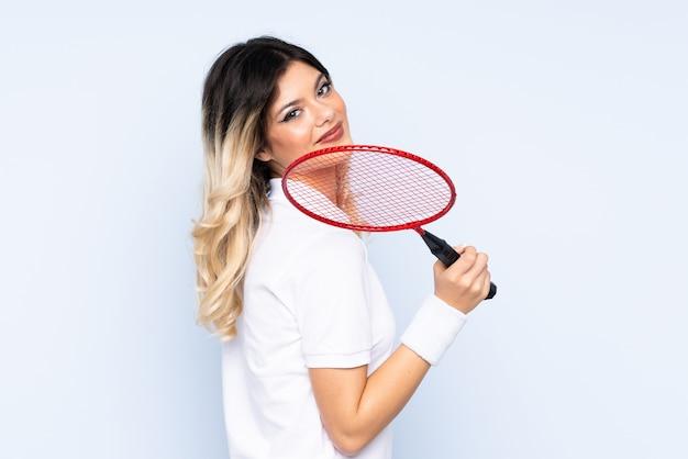 Nastolatek dziewczyna bawić się badminton odizolowywającego na błękit ścianie