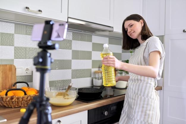 Nastolatek dziewczyna, bloger kulinarny gotowanie naleśników z pomarańczą w domu w kuchni, filmowanie przepisu wideo. kobieta z patelnią w pobliżu pieca. hobby, kanał wideo z obserwującymi, dziećmi i nastolatkami