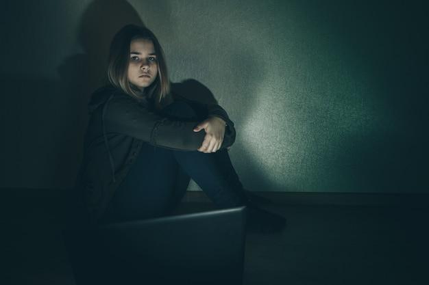 Nastolatek dziewczyna cierpi internet cyberprzemocy przestraszony i przygnębiony cyberprzemoc. obraz dziewczyny z rozpaczy poniżonej w internecie przez kolegę z klasy. młoda nastolatka płacze przed laptopem