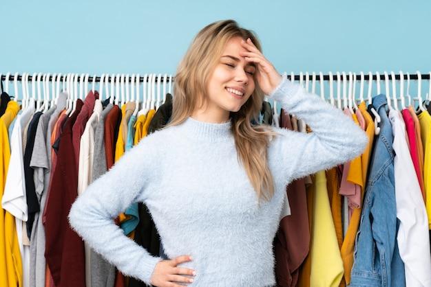 Nastolatek dziewczyna kupuje niektóre odziewa na błękit ścianie ono uśmiecha się dużo