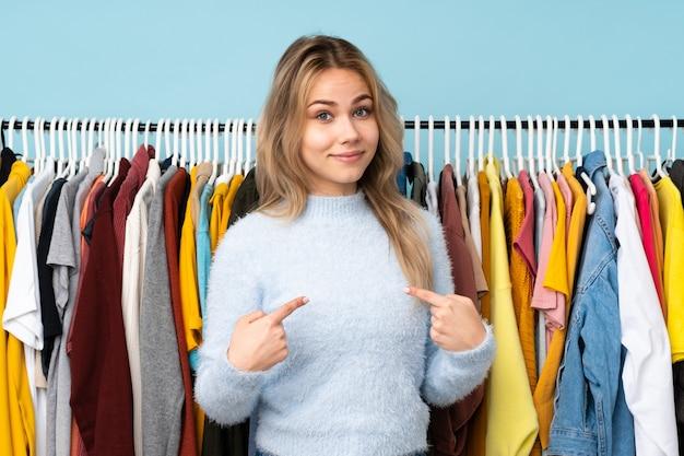 Nastolatek dziewczyna kupuje niektóre ubrania na błękicie wskazuje na siebie