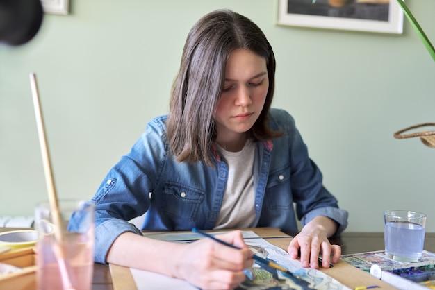 Nastolatek dziewczyna maluje akwarelami, siedząc w domu przy stole. sztuka, edukacja, kreatywność, hobby nastolatków