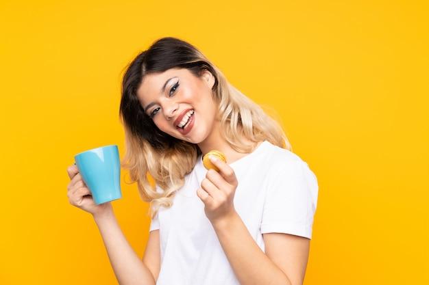 Nastolatek dziewczyna na żółty mur trzymając kolorowe francuskie macarons i szklankę mleka