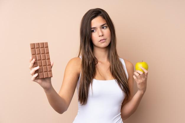 Nastolatek dziewczyna nad odosobnioną ścianą ma wątpliwości podczas gdy brać czekoladową pastylkę w jednej ręce i jabłko w drugiej
