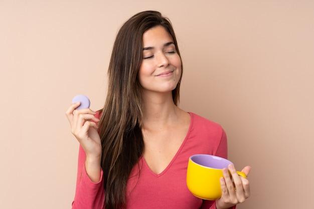 Nastolatek dziewczyna nad odosobnioną ścianą trzyma kolorowych francuskich macarons i filiżankę mleka