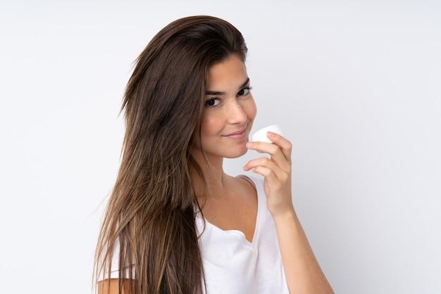 Nastolatek dziewczyna nad odosobnioną ścianą z moisturizer i wąchać je