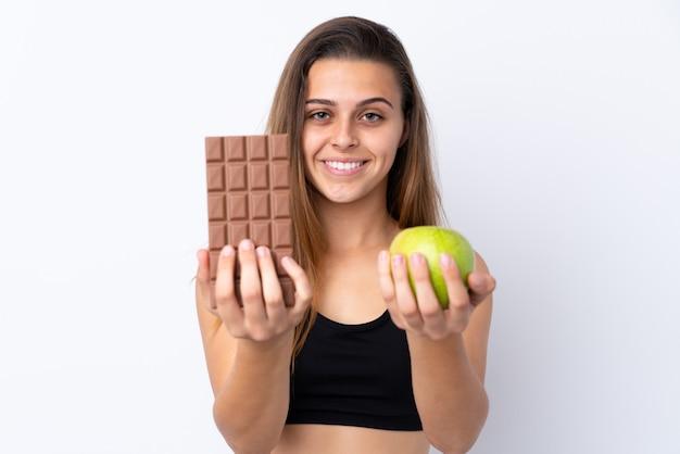 Nastolatek dziewczyna nad odosobnionym bielem bierze czekoladową pastylkę w jednej ręce i jabłko w drugiej