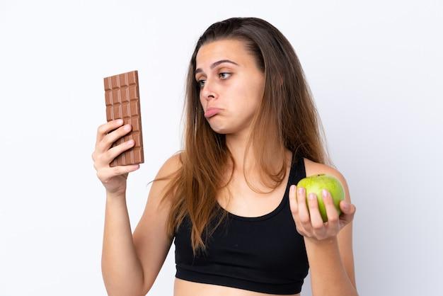 Nastolatek dziewczyna nad odosobnionym bielem ma wątpliwości podczas gdy brać czekoladową pastylkę w jednej ręce i jabłko w drugiej