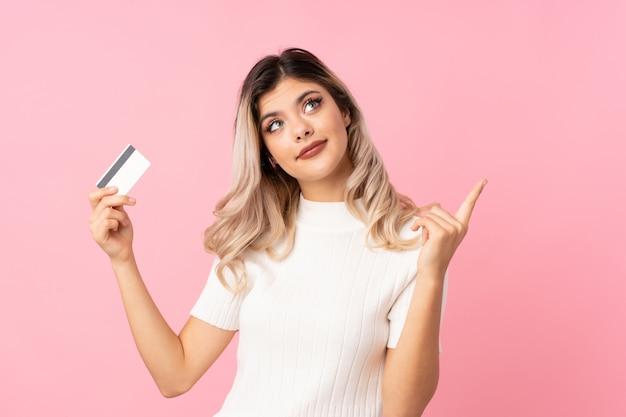 Nastolatek dziewczyna nad odosobnionym różowym tłem trzyma kredytową kartę