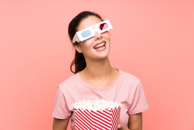 Nastolatek dziewczyna nad odosobnionymi menchii ściany łasowania popkornami z 3d szkłami
