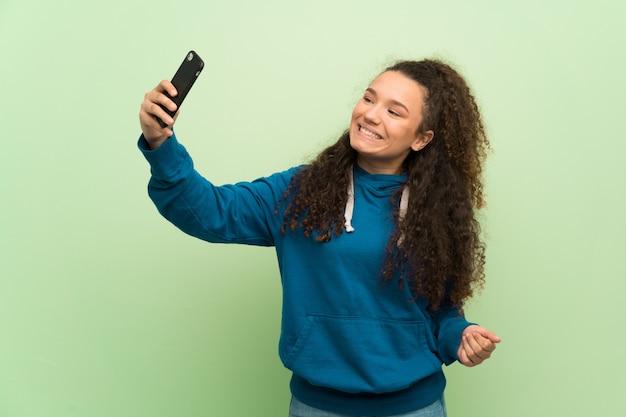 Nastolatek dziewczyna nad zieloną ścianą robi selfie