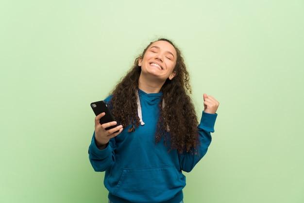 Nastolatek dziewczyna nad zieloną ścianą świętuje zwycięstwo z telefonu komórkowego