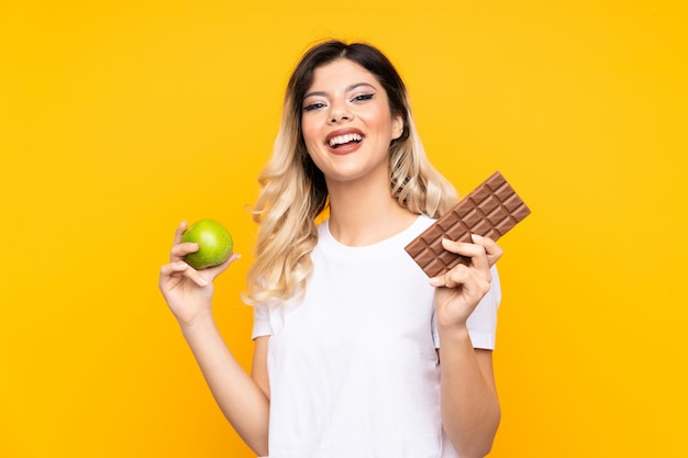 Nastolatek dziewczyna odizolowywająca na kolor żółty ścianie ma wątpliwości podczas gdy brać czekoladową pastylkę w jednej ręce i jabłko w drugiej