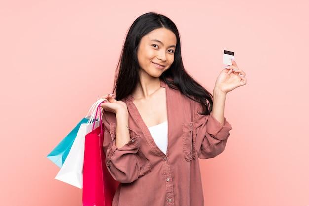 Nastolatek dziewczyna odizolowywająca na różowych mień torba na zakupy i kredytowej karcie