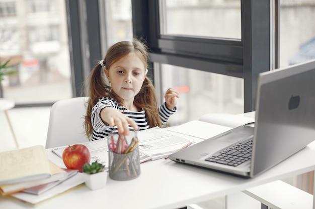 Nastolatek dziewczyna patrząc na laptopa. chiln w okresie kwarantanny podczas pandemii. nauka w domu. dystans społeczny. test szkolny online.