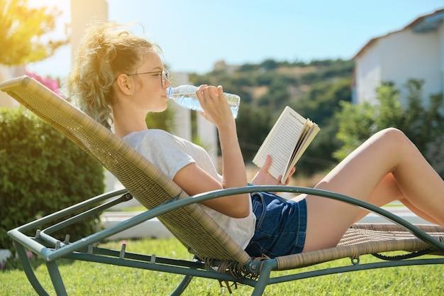 Nastolatek dziewczyna relaks na świeżym powietrzu siedząc w fotelu rattanowym na zielonym trawniku, czytając książkę i wodę pitną z butelki