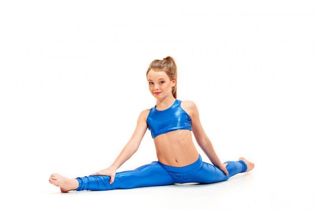 Nastolatek dziewczyna robi gimnastyk ćwiczeniom odizolowywającym na biel ścianie