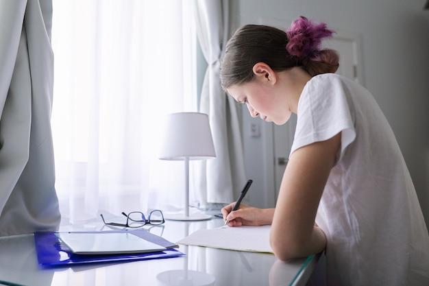 Nastolatek dziewczyna siedzi, studiując przy biurku w domu w pobliżu okna