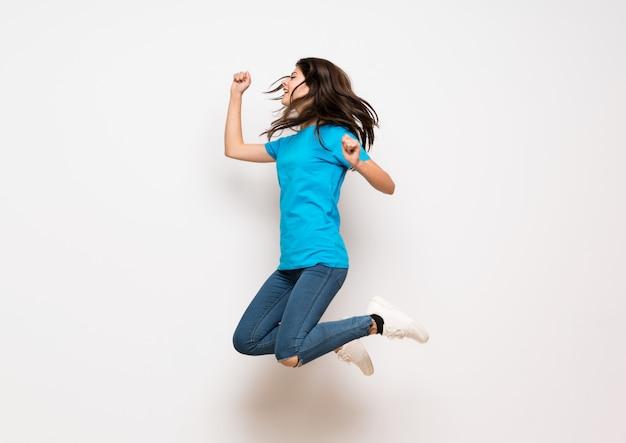 Nastolatek dziewczyna skacze nad odosobnioną biel ścianą