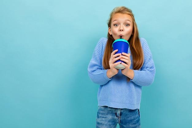 Nastolatek dziewczyna szczęśliwie pije przez słomkę ze szkła na niebieskim tle