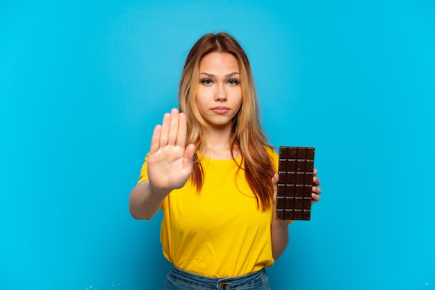 Nastolatek dziewczyna trzyma czekoladę na białym tle