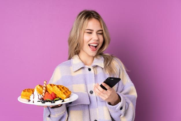 Nastolatek dziewczyna trzyma gofry na fioletowym tle z telefonu w pozycji zwycięstwa