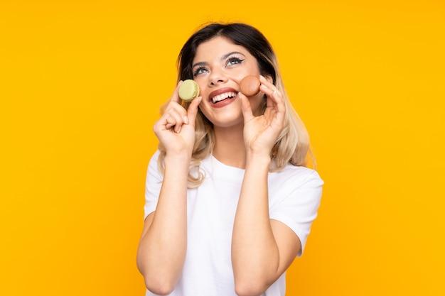 Nastolatek dziewczyna trzyma kolor żółty francuskich macarons i przyglądającego up na kolor żółty ścianie
