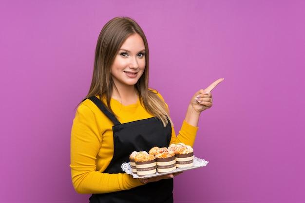 Nastolatek dziewczyna trzyma mnóstwo różnych mini ciasta na izolowanych fioletowe ściany palcem wskazującym na bok