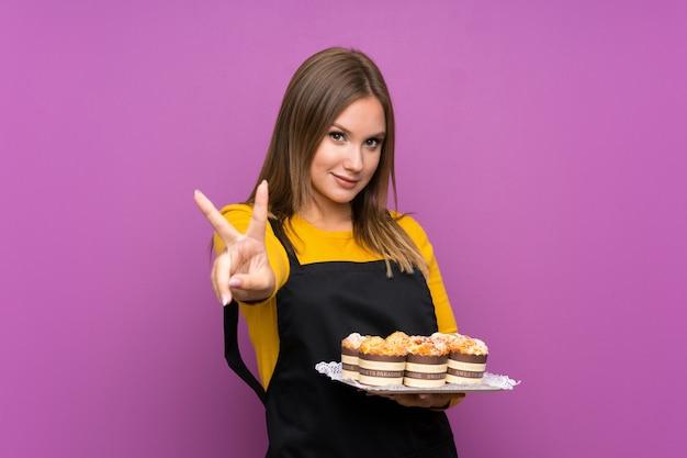 Nastolatek dziewczyna trzyma mnóstwo różnych mini ciasta na pojedyncze fioletowe ściany, uśmiechając się i pokazując znak zwycięstwa