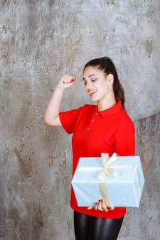 Nastolatek dziewczyna trzyma niebieskie pudełko owinięte białą wstążką i pokazuje znak ręki przyjemności.