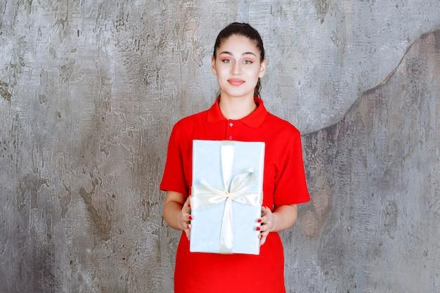 Nastolatek dziewczyna trzyma niebieskie pudełko owinięte białą wstążką.