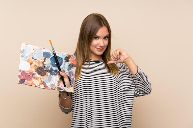 Nastolatek dziewczyna trzyma paletę nad odosobnionym tłem dumnym i samozadowolonym