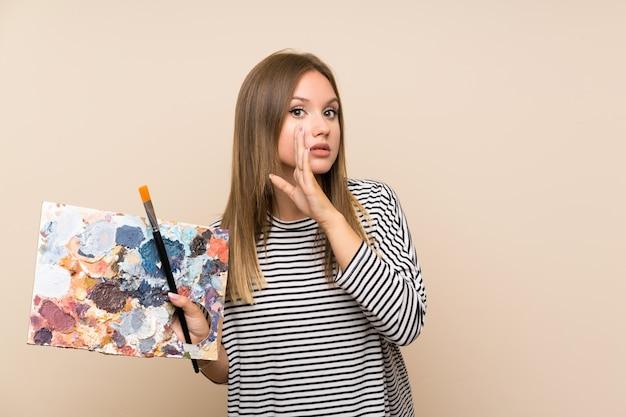 Nastolatek dziewczyna trzyma paletę nad odosobnionym tłem szepcze coś