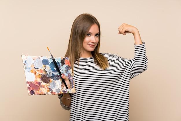 Nastolatek dziewczyna trzyma paletę robi silnemu gestowi