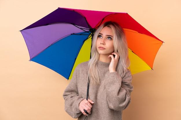 Nastolatek dziewczyna trzyma parasol nad ścianą myśleć pomysł