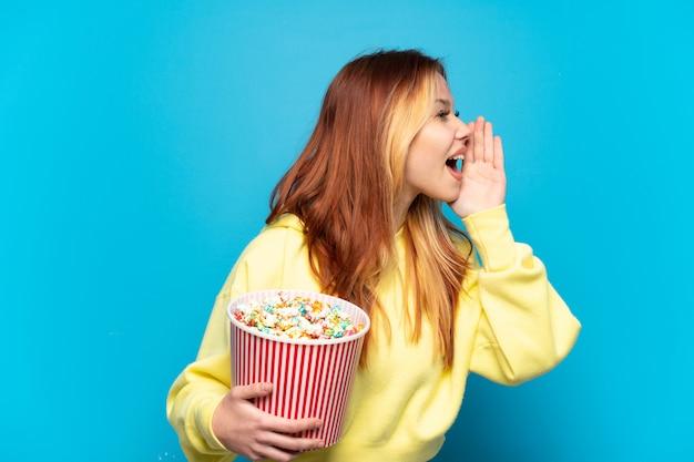 Nastolatek dziewczyna trzyma popcorns na na białym tle niebieskim tle krzycząc z szeroko otwartymi ustami na bok